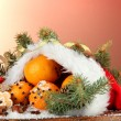 Christmas composition with oranges and fir tree in Santa Claus hat - Stock Photo