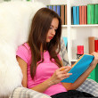 Portrait of female reading book at home -  