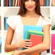 Young attractive female student holding her school books in library — Stock Photo #16026201