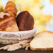 Fresh bread in basket on wooden table on natural background - Stock Photo
