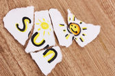 Torn paper with words Sun close-up on wooden table — Stock Photo