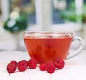Tea with raspberries on table on bright background — Stock Photo
