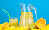 Citrus lemonade in glass and pitcher of citrus around on yellow fabric on blue background — Stock Photo