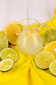 Citrus lemonade in glass pitcher of citrus around on yellow fabric on white wooden table close-up — Stockfoto