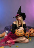 Halloween witch holding pumpkin on color background — Stock Photo
