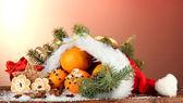 Vánoční složení pomeranče a jedle v santa claus klobouk — Stock fotografie