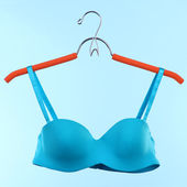 Elegant bra on hanger on blue background — Stock Photo