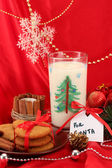 Cookies for Santa: Conceptual image of ginger cookies, milk and christmas decoration on red background — Stock fotografie
