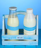 Milk in bottles in wooden box on blue wooden table on blue background — Stock Photo