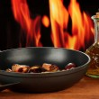 Roasted chestnuts in the pan and decanter with oil, salt and pepper on wooden table close-up — Stock Photo #16235067