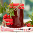 Jars with hip roses jam and ripe berries, on wooden table — Stock Photo #16235173