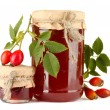 Jars with hip roses jam and ripe berries, isolated on white — Stock Photo #16235181