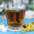 A cup of tea with immortelle on blue wooden table on window background - Stock Photo