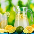 Citrus lemonade in pitcher and glass of citrus around on natural wooden table on blue background — Lizenzfreies Foto