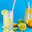 Citrus lemonade in pitcher and glass of citrus around on wooden table on blue background — Stok fotoğraf