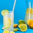 Citrus lemonade in pitcher and glass of citrus around on wooden table on blue background — Lizenzfreies Foto