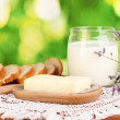 Butter on wooden holder surrounded by bread and milk on natural background — Stock Photo