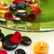 Spa stones with rose petals and candles in water on plate, isolated on white — Stock Photo