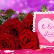 Beautiful bouquet of roses with valentine on pink fabric on purple background close-up — Stock Photo #16235583