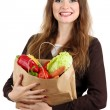 Woman holding a grocery bag full of fresh vegetables isolated on white — Stock Photo #16235735