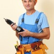 Builder with drill on wall background — Stock Photo #16235863