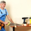Builder sawing boards on table on wall background — Stock Photo #16235871