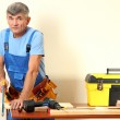 Builder sawing boards on table on wall background — Stock Photo #16235873