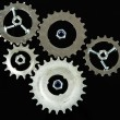 Metal cogwheels, nuts and bolts isolated on black - Stock Photo