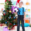 Little boy in Santa hat stands near Christmas tree with football ball — Stock Photo #16236631