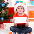 Little boy in Santa hat writes letter to Santa Claus — Stock Photo #16236635