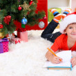 Little boy in Santa hat writes letter to Santa Claus — Stock Photo #16236639