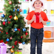 Little boy in Santa hat stands near Christmas tree with gift in his hands — Stock Photo #16236641