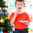 Little boy near Christmas tree eats cookies — Stock Photo #16236647