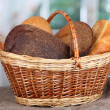 Fresh bread in basket on wooden table on window background - Stock Photo