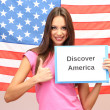 Young woman young woman holding tablet on background of American flag — Stock Photo