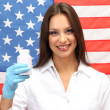 Portrait of female doctor or scientist showing and analyzing pills over American Flag background — Stock Photo #16237047