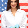 Portrait of female doctor or scientist showing and analyzing pills over American Flag background — Stock Photo #16237059