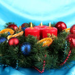 Beautiful Christmas wreath on blue fabric background — Stock Photo