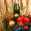 Beautiful Christmas wreath in composition with champagne on gold fabric background — Stock Photo