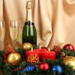 Beautiful Christmas wreath in composition with champagne on gold fabric background - Photo