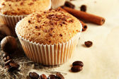 Tasty muffin cakes with chocolate, spices and coffee seeds, on beige background — Stock Photo
