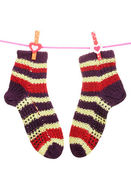Pair of knit striped socks hanging on a rope isolated on white — Stock Photo