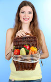 Beautiful woman with vegetables in wicker basket on blue background — Stockfoto