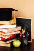 Books and magister cap against school board on wooden table on beige background — Stock Photo