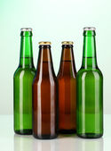 Coloured glass beer bottles on green background — Stock Photo