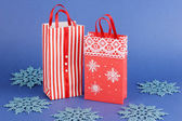 Christmas paper bags for gifts on blue background — Stock Photo