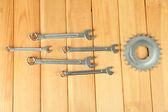 Roda dentada de metal e chaves inglesas em fundo de madeira — Fotografia Stock