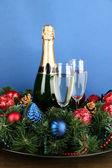 красивых рождественский венок в композиции с шампанским на синем фоне — Стоковое фото