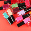 Group of bright nail polishes, on red background — Stock Photo