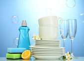 Empty clean plates, glasses and cups with dishwashing liquid, sponges and lemon on blue background — Stock Photo